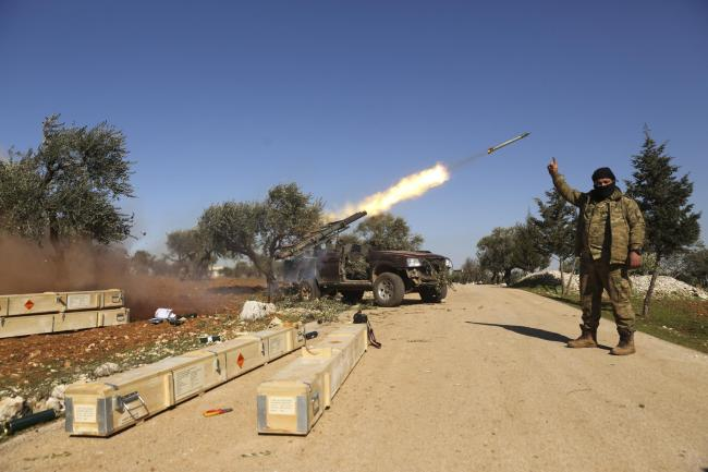 Rebel fighters fire a missile towards Syrian government positions in the province of Idlib