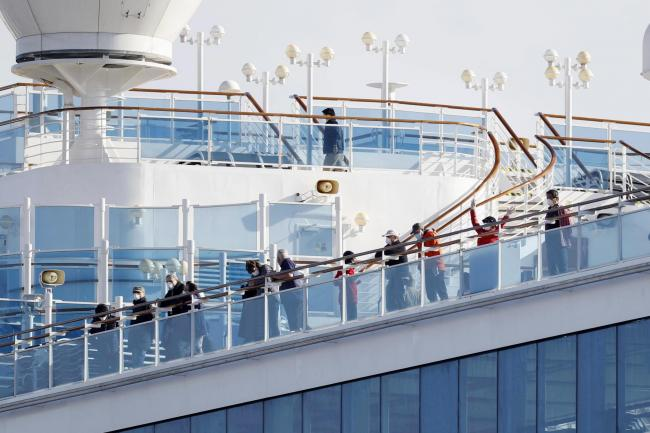 Passengers stand on the deck of the Diamond Princess cruise ship
