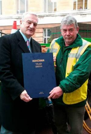 Councillor Maurice Heaster presents Roy Dunn with a commemorative book