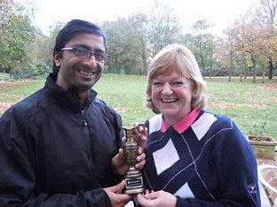 Vickesh Chauhan presents the winner's trophy to Caroline Michel