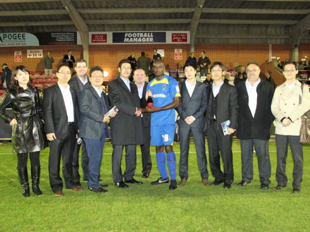 Wandsworth Guardian: Nongshim representatives presenting the man of the match award before Wimbledon's home match against Torquay