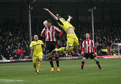 Frustrated: Bees striker Marcello Trotta gets up for header at Griffin Park on Saturday