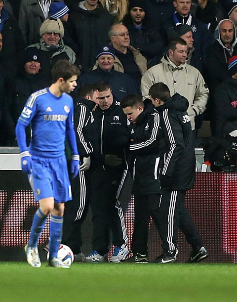Ball boy Charlie Morgan is led away after being kicked by Chelsea's Eden Hazard