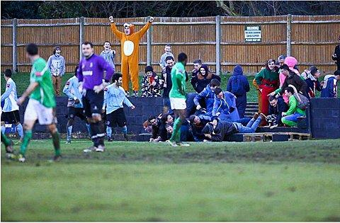 Front of the terracing collapses as Dulwich Hamlet supporters celebrate. Photo: Neil Hood