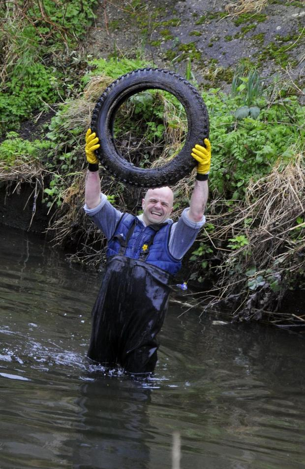 Rob Woods pulls a discarded tyre from the river