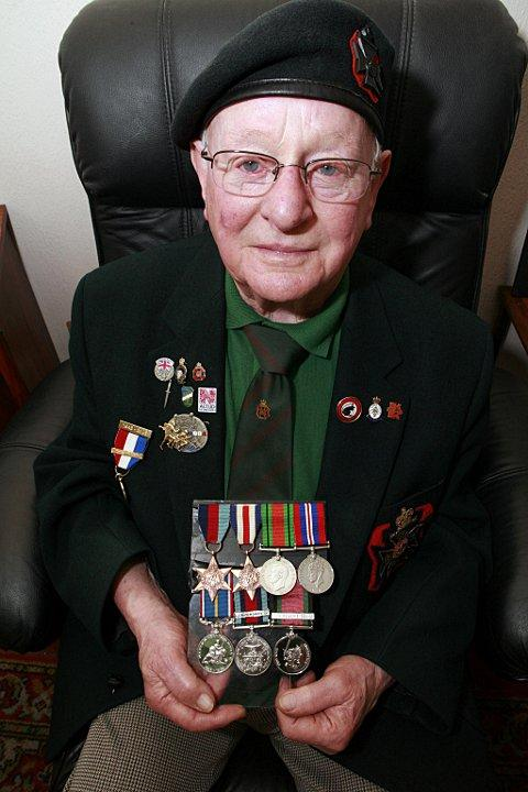 Corporal Lewer at his Southfields home with his collection of medals