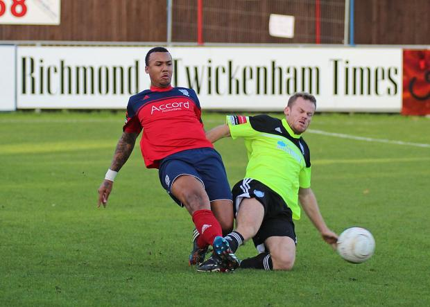 Wandsworth Guardian: On his way: Hampton and Richmond Borough's Marcus Rose nips in to dispossess Met Police striker Allan Tait, right