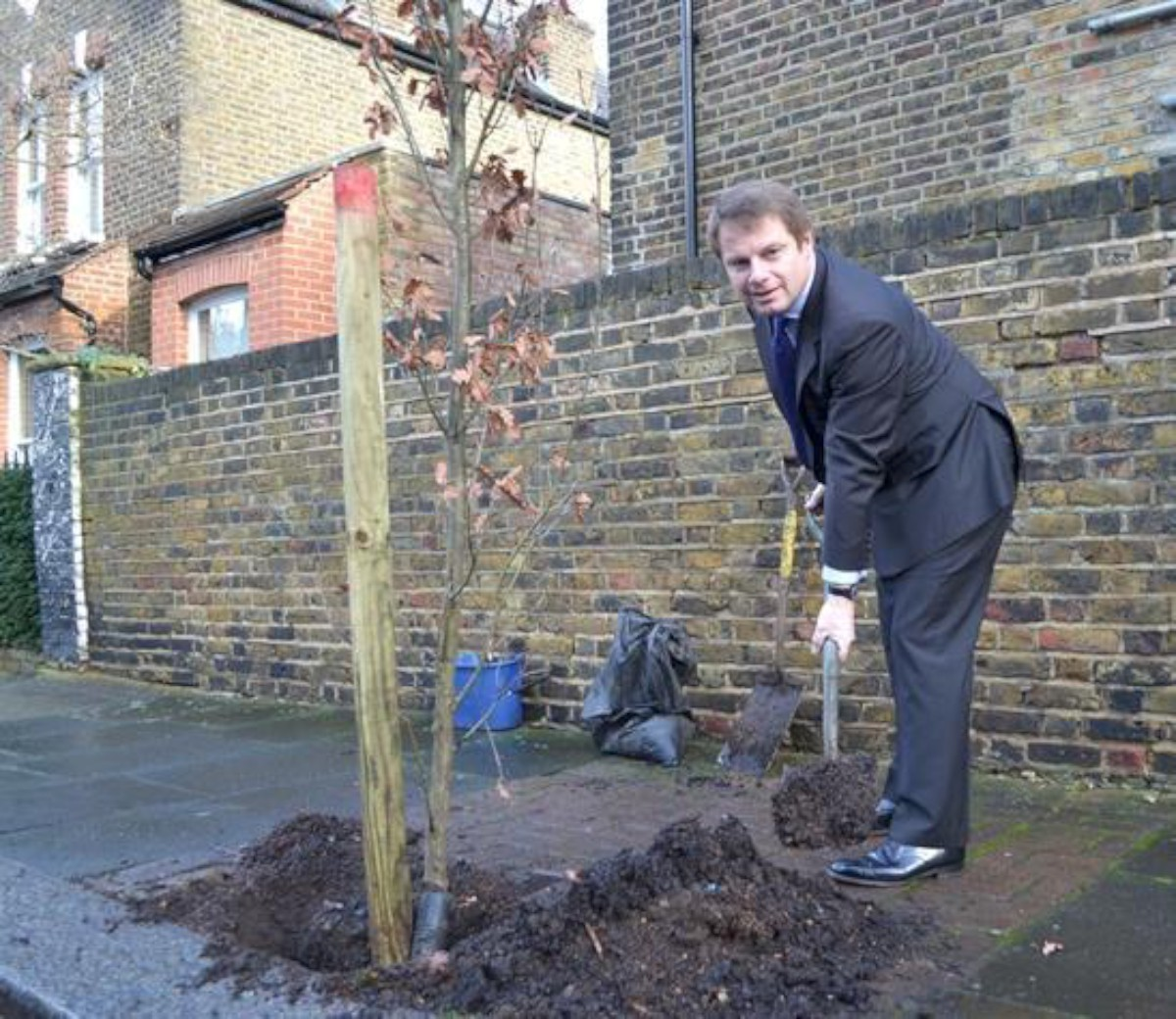 Councillor Jonathan Cook gets his hands dirty planting a tree in Battersea