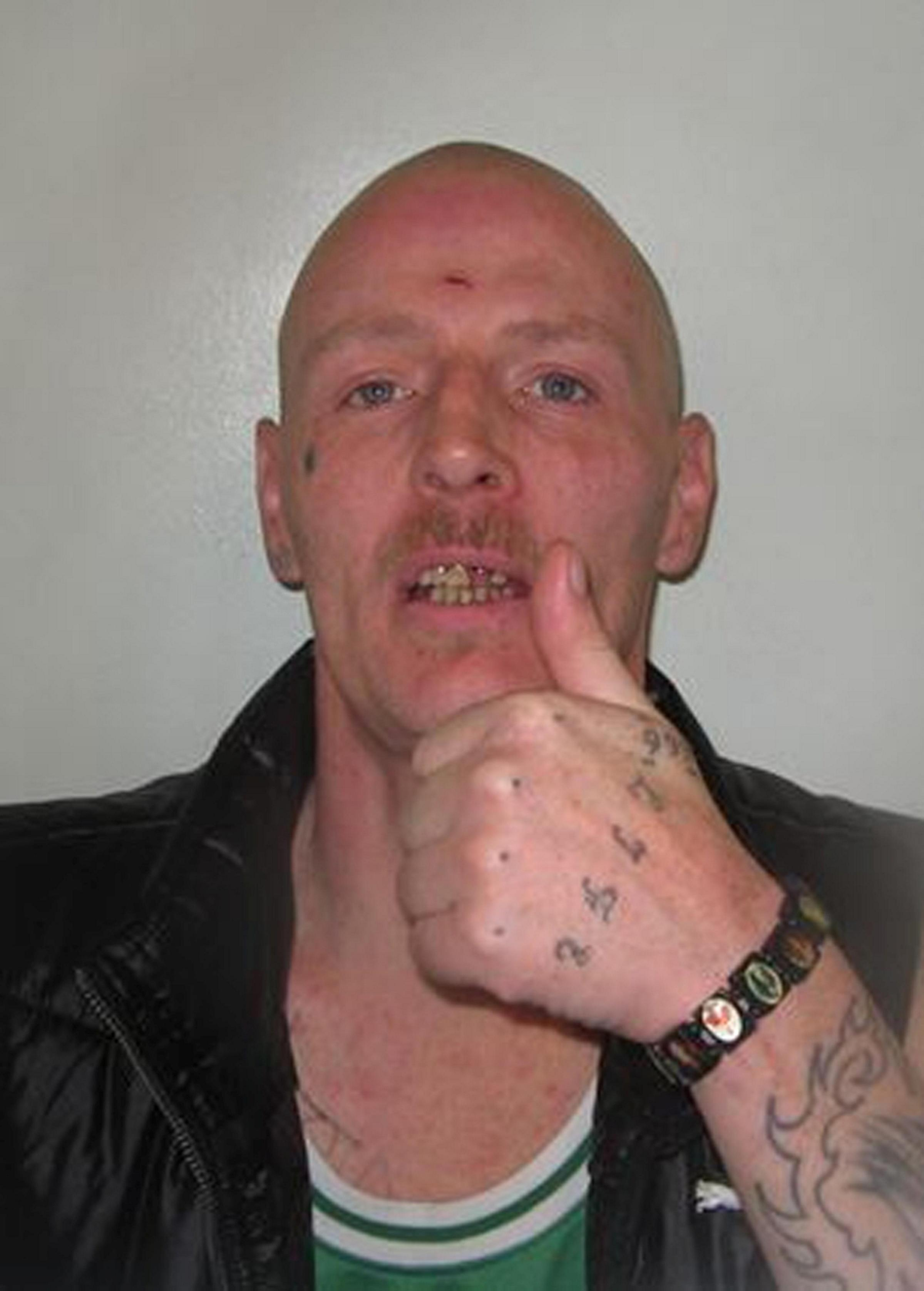 Richard Mulcahy giving thumbs up in a police mugshot. His last