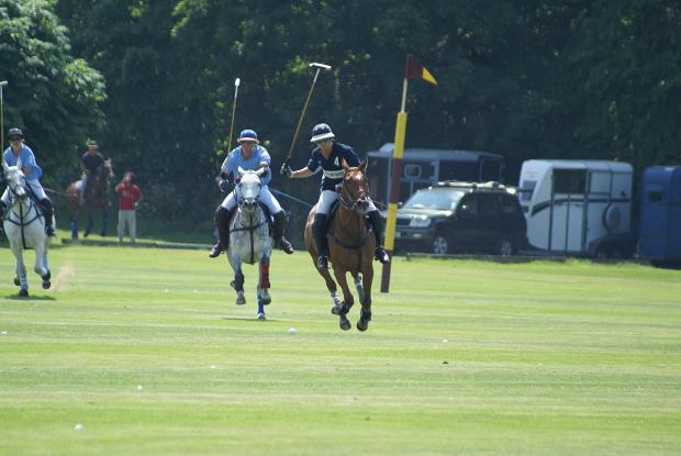 Wandsworth Guardian: On the charge: Cavaliers star Benjie Davis, light blue, gives chase as Charlie Wood launches an attack for Quadriga in the Ham House Trophy final    Picture Stuart Amos