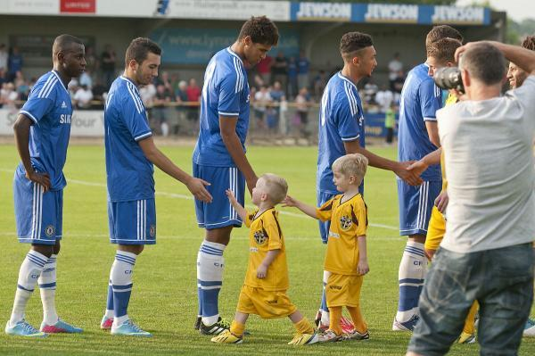Last time out: Sutton United mascots shake hands with Chelsea U21s stars
