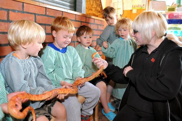 The kids sit calmly with a big snake on their laps