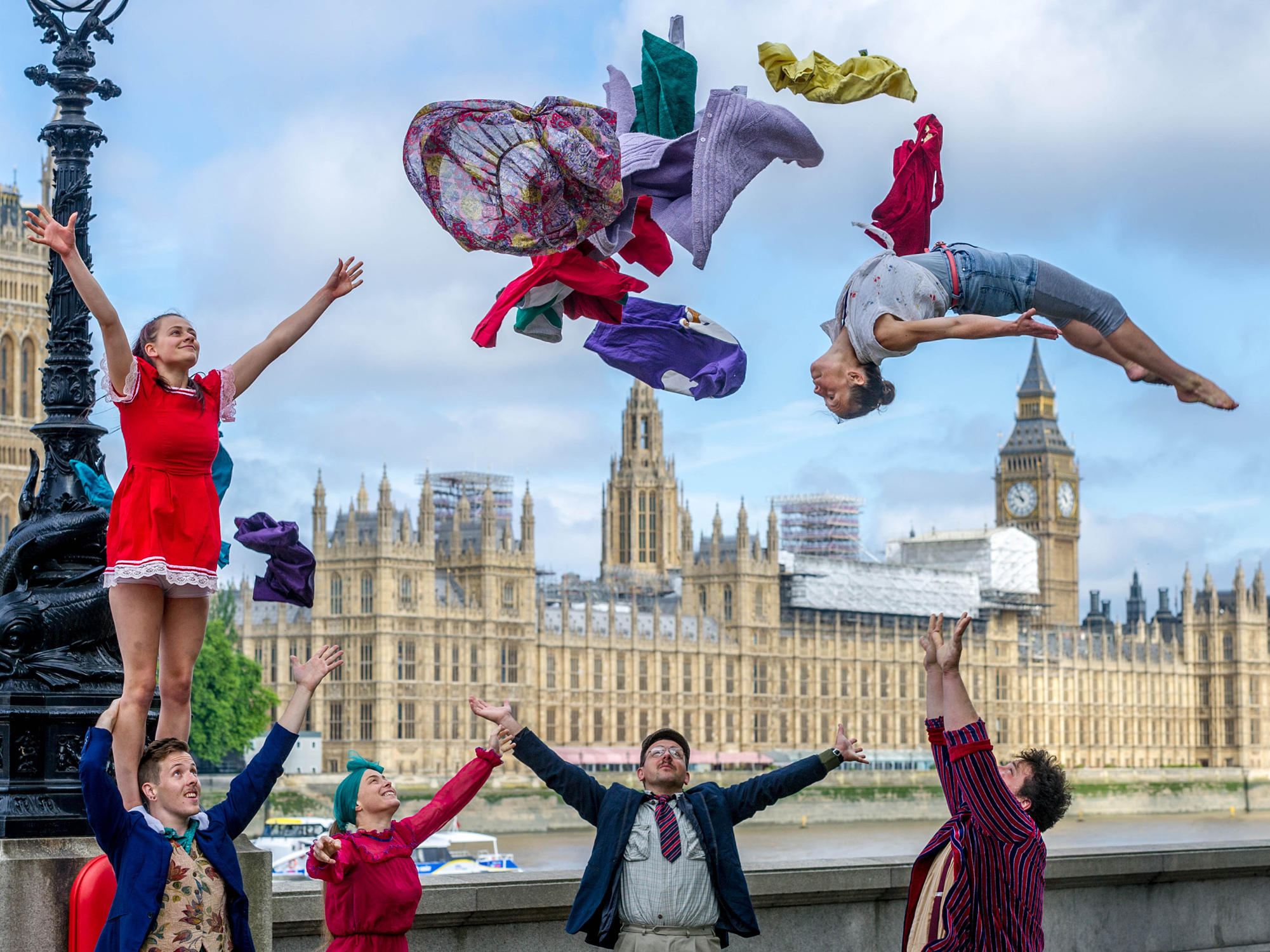 Acrobats from the group Lost in Translation perform a stunt in front of the Houses of Parliament in London